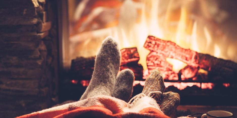toes warming under blanket in front of a lit fireplace