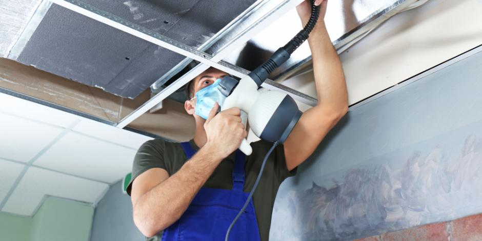 Technician cleaning duct work